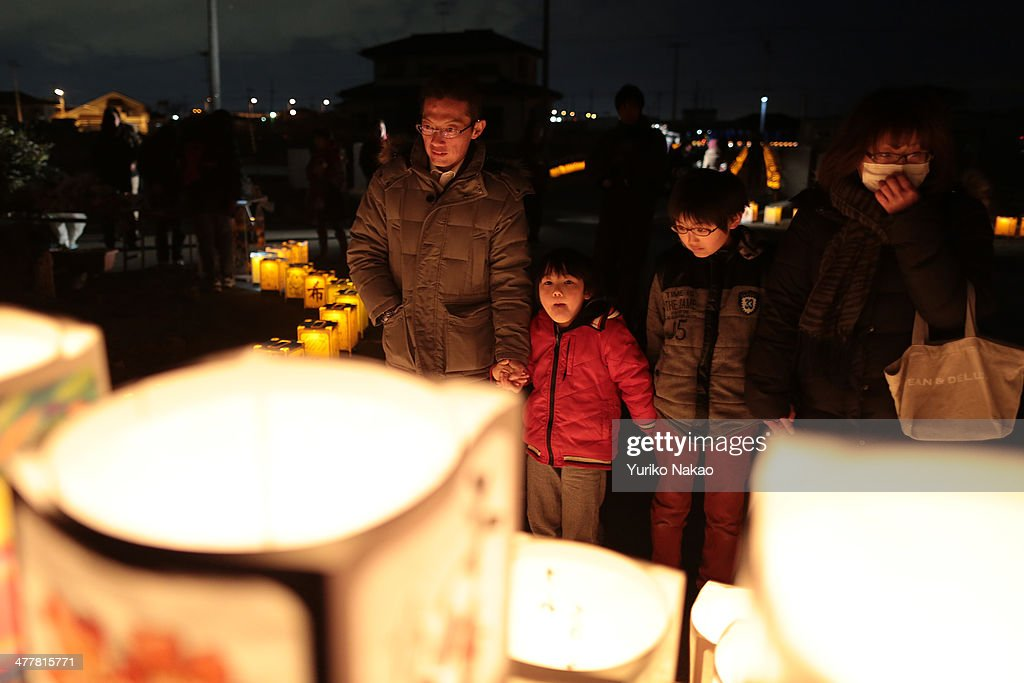 A family looks at paper lanterns during a memorial held in remembrance of victims of the March 11, 2011 earthquake and tsunami at Yuriage Junior High School on March 11, 2014 in Natori, Miyagi prefecture, Japan. On March 11 Japan commemorates the third anniversary of the magnitude 9.0 earthquake and tsunami that claimed more than 18,000 lives, and subsequent nuclear disaster at the Fukushima Daiichi Nuclear Power Plant.