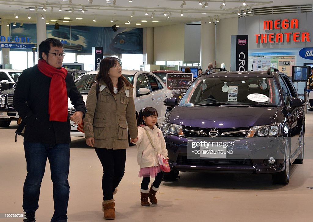 A family looks at Toyota Motor at the company's showroom in Tokyo on February 5, 2013. Toyota said its net profit quadrupled for the nine months to December as the Japanese auto giant revised upward its full-year profit and sales forecast. AFP PHOTO / Yoshikazu TSUNO