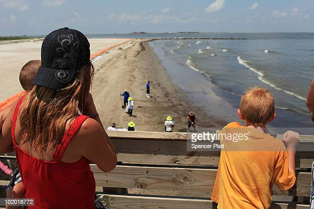 A family looks on as workers hired by BP help clean oil off the beach in a contaminated area on June 12 2010 in Grand Isle Louisiana US government...