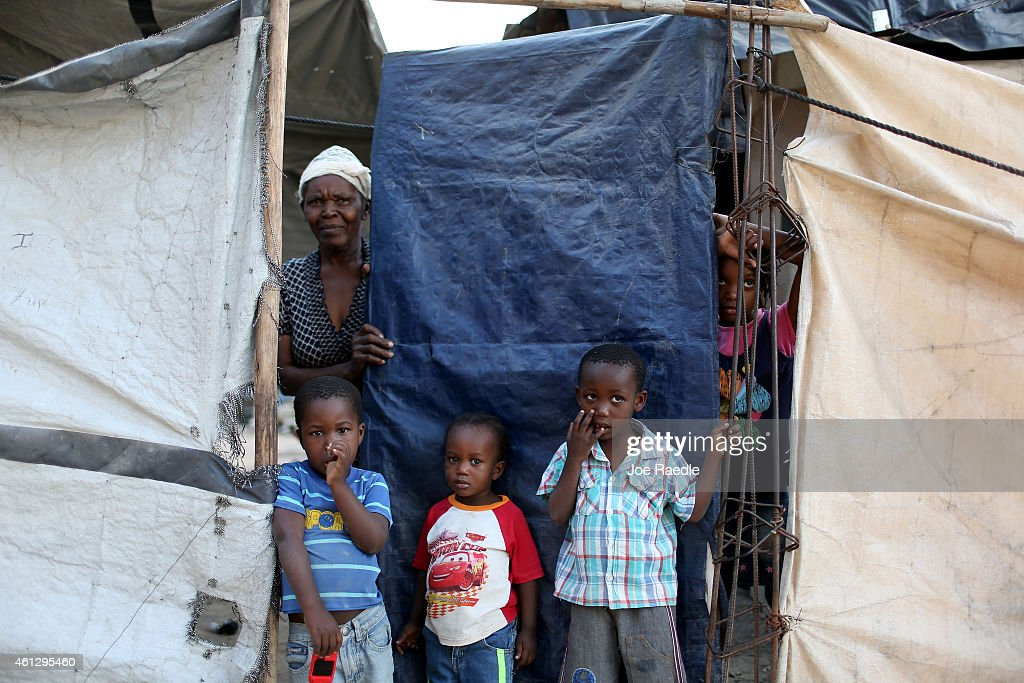 A family looks out from behind the tarp that serves as the front door to their home built over the land where their home once stood before a...