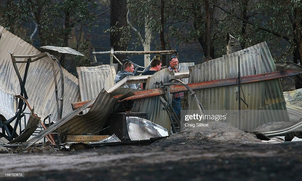 A family looks over the loss of their holiday home after a fire in the town of Seaton on January 19, 2013 in Melbourne, Australia. Bushfires in Victoria have claimed one life and destroyed several houses. Record heat continues to create extreme fire conditions throughout Australia.