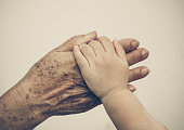 hand of a young baby touching old hand of the elderly - Love between young and old generation concept