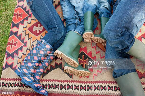 Family lying down on carpet outdoors