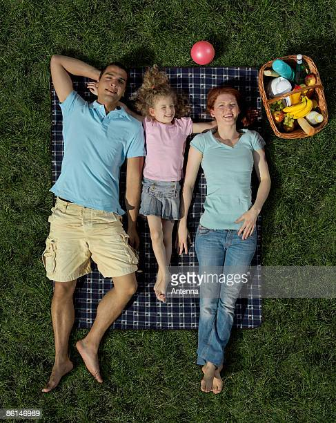 A family lying on a blanket on the grass