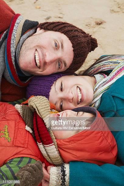 Family lying on a sandy beach in winter