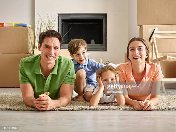 Family lying on carpet and smiling