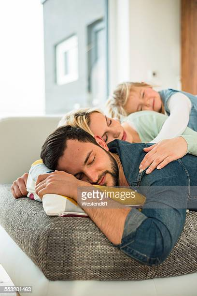 Family lying on couch on top of each other with closed eyes