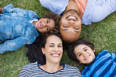 Overhead view of cheerful family lying on grass in a circle and looking at camera. High view of multiethnic family lying on grass at park. African father and hispanic mother with their smiling childre
