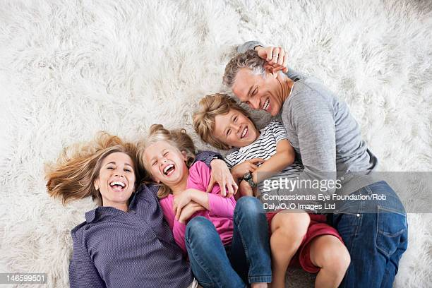 Family lying on rug in living room, laughing