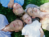 Family lying on the grass.