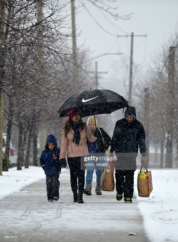 A family makes their way back to home with their groceries under a snowfall in Wheaton, Maryland, on March 6, 2013. A massive winter storm pounding the northern US on March 6, grounded 2,600 flights, closed hundreds of schools and made roadways and highways impassible. At least four people were reportedly killed in accidents on icy and snow covered roads and highways. AFP PHOTO/Jewel Samad
