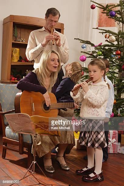 Family Making Music Around Christmas Tree