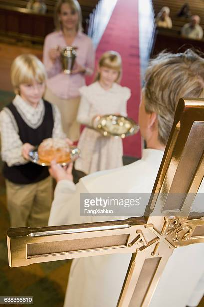 Family making offering at mass in church