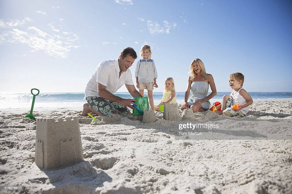 Family making sand castles on beach : Stock Photo