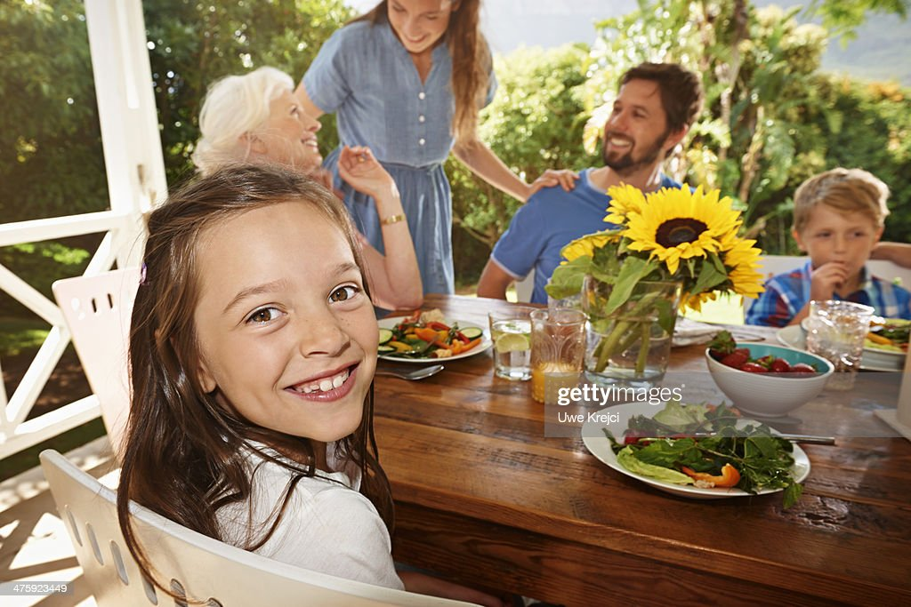 Family meal outdoors, portrait of girl smiling : Stock Photo