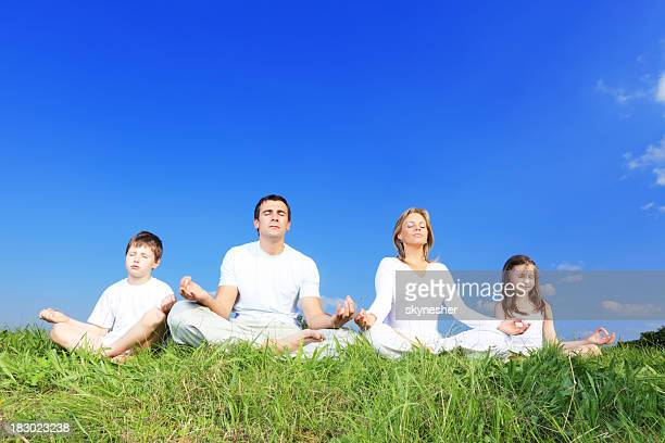 Family meditation outdoor, doing yoga.