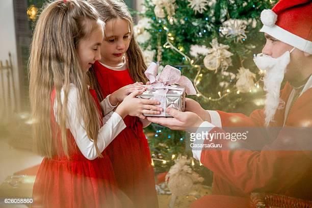 Family Member giving Christmas Presents to Little Girls