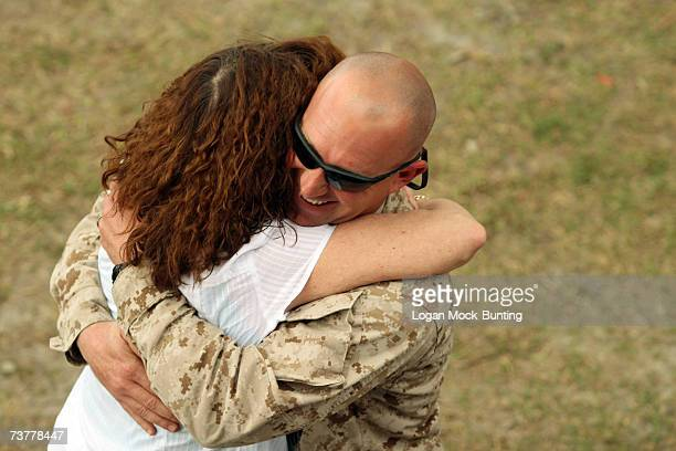 A family member greets Gunnery Sergeant Curtis Rinker of the 2nd Light Armored Reconnaissance Battalion upon arriving on April 2 2007 in Camp Lejeune...