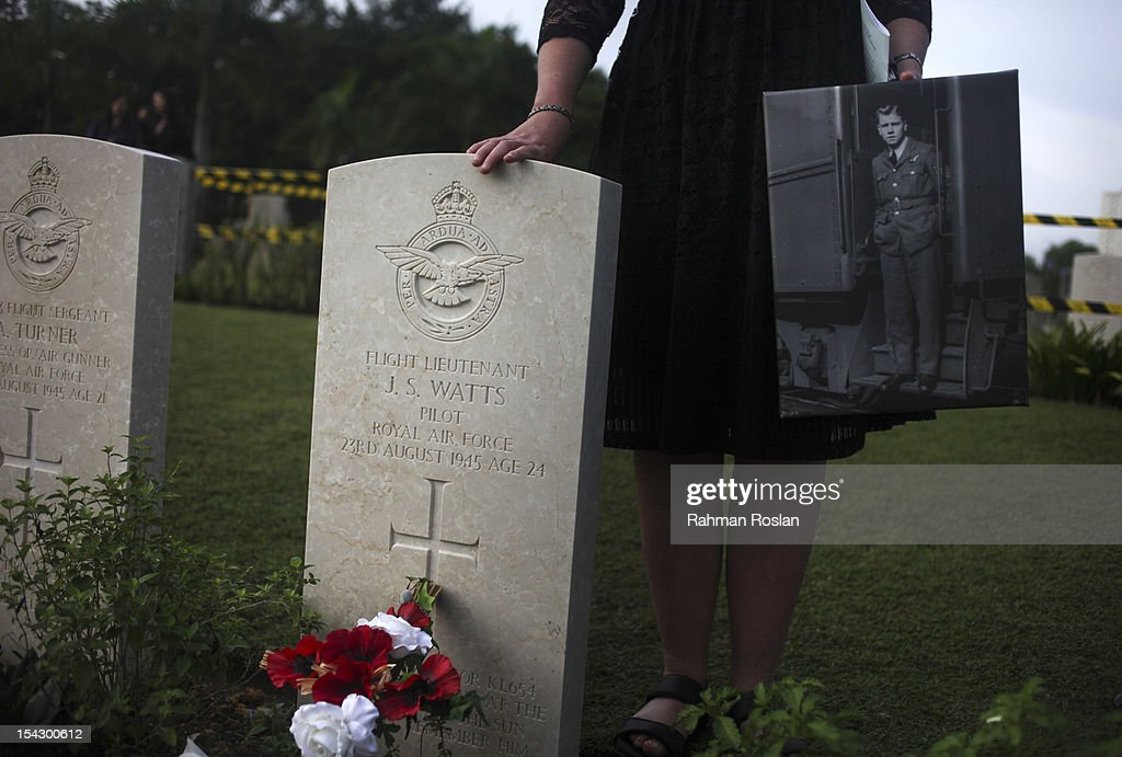 A family member holds a photograph of a late British pilot during the burial of eight RAF crew members at the Commonwealth War Cemetery on October 18, 2012 in Kuala Lumpur, Malaysia. The eight crew members were flying a B-24 Liberator on August 23, 1945, eight days after Japan surrendered in World War II, when the plane crashed and was lost near Kuala Pilah, Malaysia. The crash site was undiscovered until the 1990s and human remains were found in 2009 after a detailed investigation.