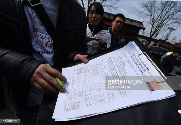 A family member of a Chinese passenger from the missing Malaysia Airlines flight MH370 shows off a signed petition to urge for the continuation of...