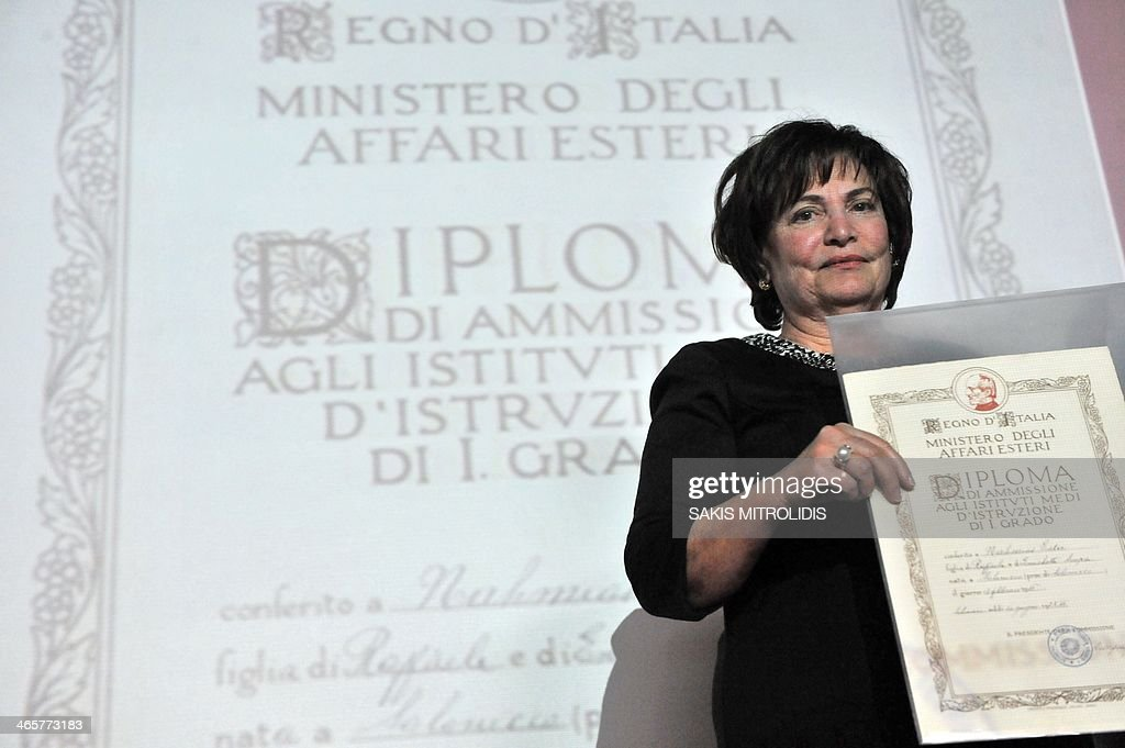 A family member of Jewish Community of Thessaloniki takes the diploma of her ancestors from the Italian Institute of Culture on the occasion of Remembrance Day in Thessaloniki on January 29, 2014. In the Institute were recovered among the papers of the High School Gymnasium, Umberto I - school Italian that the 1930s was located in the same building that now houses the Institute Italian, 155 degrees of Jewish children never picked up by the interested parties. During World War II, about 54,000 Jews of Thessaloniki were deported to Nazi concentration camps. At the end of the war, the city counted only 2,000 Jews : approximately 98% of the Jewish population, which numbered many Italian families, had been exterminated. AFP PHOTO /Sakis Mitrolidis