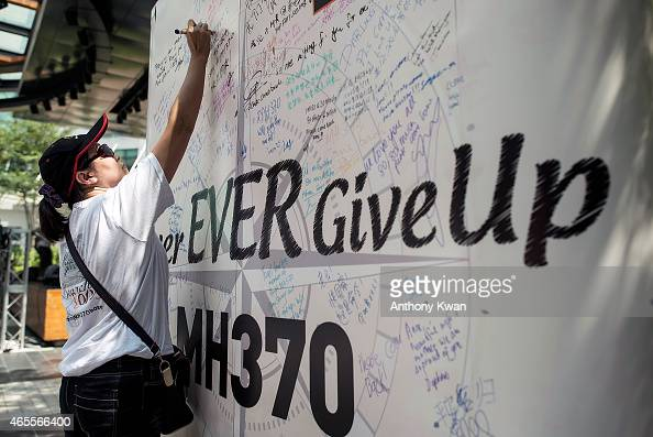 A family member of victim of MH370 plane crash writes a on a message board during a memorial event MH370 Day of Remembrance at The Square of Publika...
