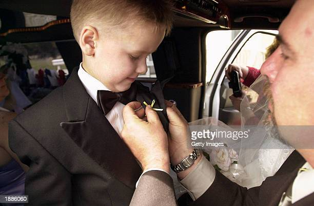 A family member pins a yellow ribbon on the lapel of Steven Millett at the wedding for Ed and Wanda Millett March 30 2003 in Lewes Beach Delaware The...