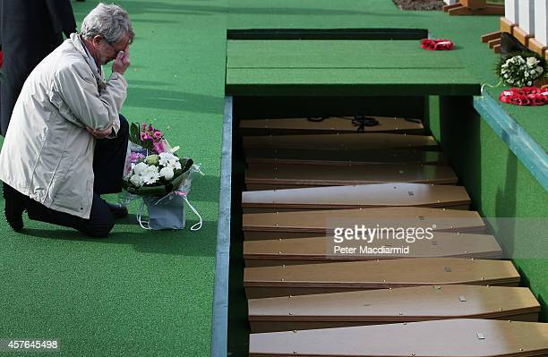 A family member places a floral tribute next to coffins containing the remains of 15 British World War One soldiers during a reburial ceremony at the...