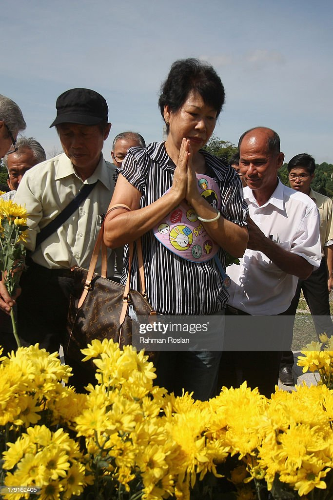 Family members and friends place bouquets of flowers on the memorial ground during the World War II Japanese Invasion Day Commemoration Ceremony on September 1, 2013 in Nilai, Malaysia. Many Malaysians still remember the atrocities inflicted by the Japanese army in Malaysia from September 1, 1941 for three years and eight months during World War II.