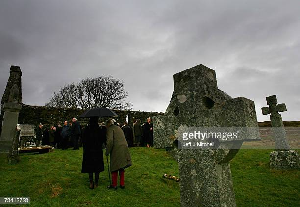 Family members and friends stand at the graveside of Chief of Clan MacLeod John MacLeod at the burial ground of the old ruined church at Kilmuir...