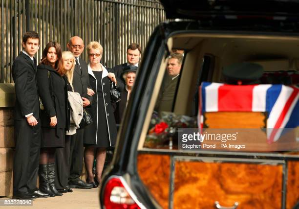 Family members and mourners look on as the coffin of Rifleman Jamie Gunn arrives at St Mary's Church in Monmouth for the funeral service Rifleman...