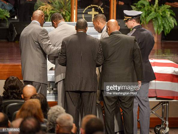 Family members and officials gather over the casket for one last look before it is closed during funeral services for PGPD Detective Jacai Colson...