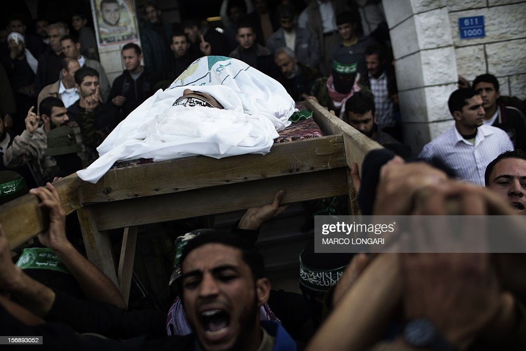 Family members and Palestinian militants of Hamas' armed wing, the Ezzedine al-Qassam Brigades, carry the body of one of their leaders, Judah Shamallah, during his funeral procession in Gaza City on November 24, 2012. Shamallah died overnight from injuries he endured from the week-long confrontation between Israel and Gaza militants that killed at least 160 people.