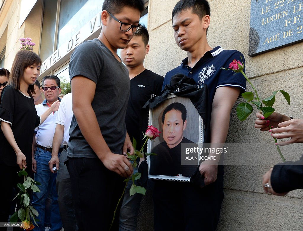 Family members and relatives hold a portrait of Chinese Zhang Chaolin as people light candles and lay flowers during a tribute ceremony outside the...