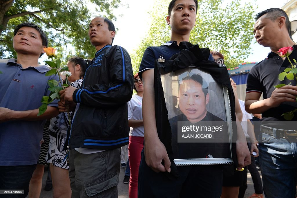 Family members and relatives hold the portrait of Chinese Zhang Chaolin during a tribute ceremony outside the city hall in Aubervilliers northeastern...