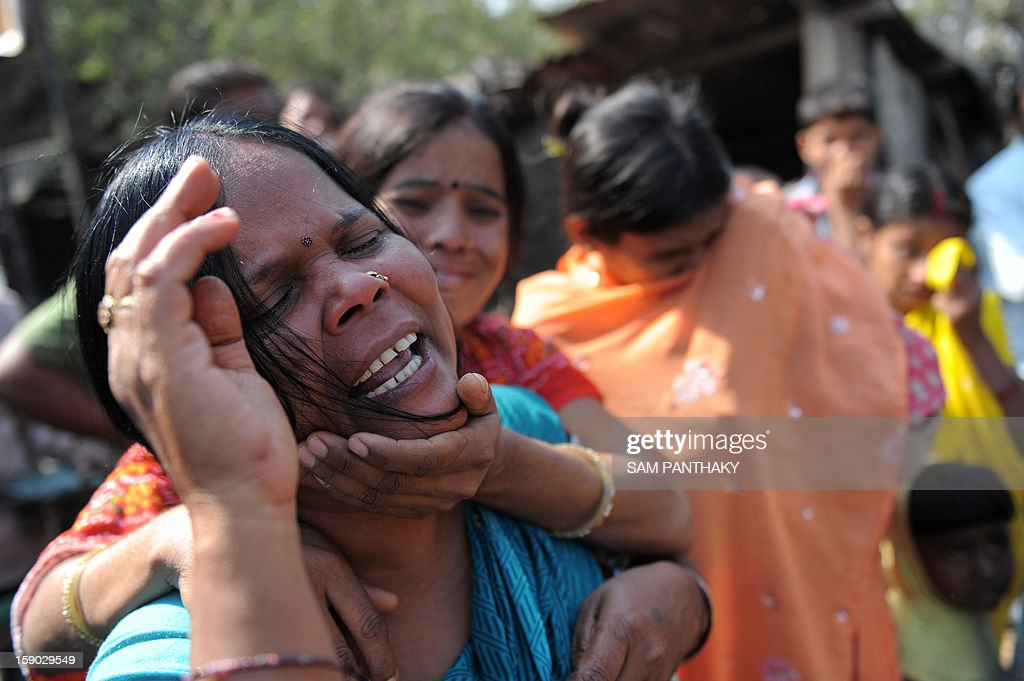 Family members and relatives of missing workers react outside the Indian Oil Corporation (IOC) plant at Hajira near Surat, some 275 kms from Ahmedabad on January 6, 2013. Three persons were killed in a major fire in a storage tank of IOC terminal, which was contained after a 21-hour operation by fire brigade team, officials said according to the Press Trust of India (PTI). AFP PHOTO / Sam PANTHAKY
