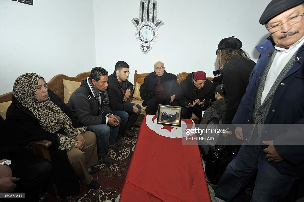 Family members and supporters mourn on February 7, 2013 around the of coffin of Chokri Belaid, an outspoken opposition leader who was assassinated the previous day, at his family home in the Tunisian capital's suburb of Jebel Jelloud. Police was deployed in force in Tunis amid fears the murder of Belaid could reignite nationwide violence, as the ruling Islamists broke ranks over how to defuse the crisis. Belaid's family said his funeral will take place on February 8 after the main weekly prayers.