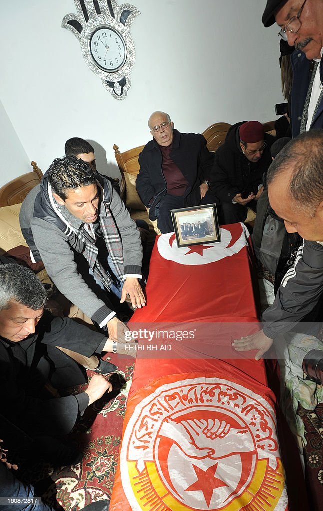 Family members and supporters mourn on February 7, 2013 around the of coffin of Chokri Belaid, an outspoken opposition leader who was assassinated the previous day, at his family home in the Tunisian capital's suburb of Jebel Jelloud. Police was deployed in force in Tunis amid fears the murder of Belaid could reignite nationwide violence, as the ruling Islamists broke ranks over how to defuse the crisis. Belaid's family said his funeral will take place on February 8 after the main weekly prayers. AFP PHOTO / FETHI BELAID