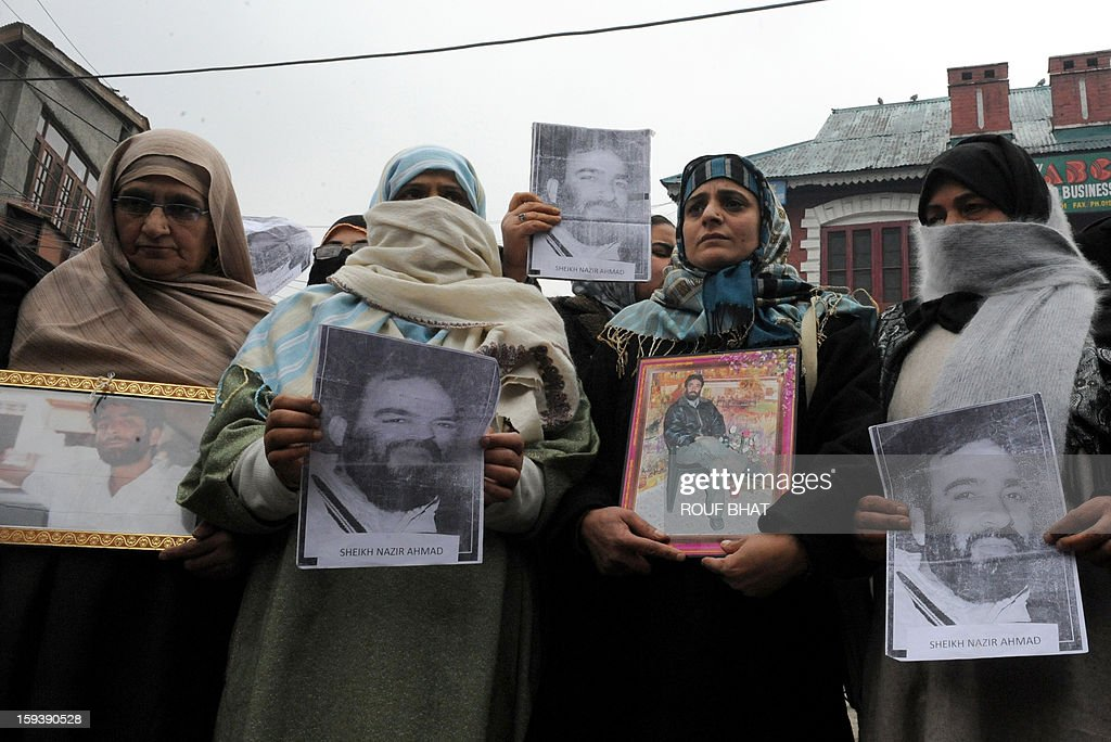 Family members and supporters of the pro-independence Jammu and Kashmir Libration Front (JKLF)hold photographs during a 'jail bharo' agitation to tempt police for their arrest in Srinagar on January 13, 2013.The agitation was held to protest against the life sentences to Kashmiri prisoners by the Indian courts. At least 29 Kashmiri men are in jails serving life sentences, according to Kashmiri human rights group. AFP PHOTO/Rouf BHAT