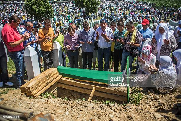 Family members and volunteers pray over one of the 136 coffins of newlyidentified victims of the 1995 Srebrenica massacre next to its final grave...