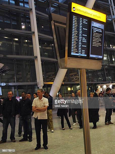 Family members and wellwishers look at the arrivals board at London's Heathrow terminal 5 waiting for the first passengers at London's Heathrow...