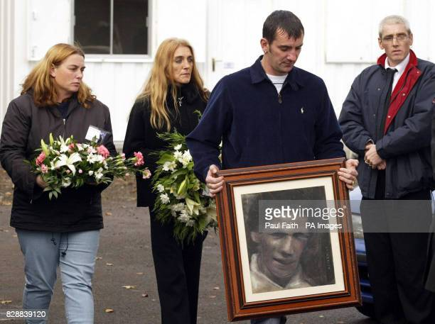 Family members carry flowers and a picture of their mother Jean McConville as the coffin is carried into her sons house at Crumlin Co Antrim Mrs...