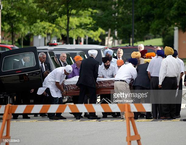 Family members escort one of the six caskets into the public visitation as family friends and public pay respect to the six victims in the mass...