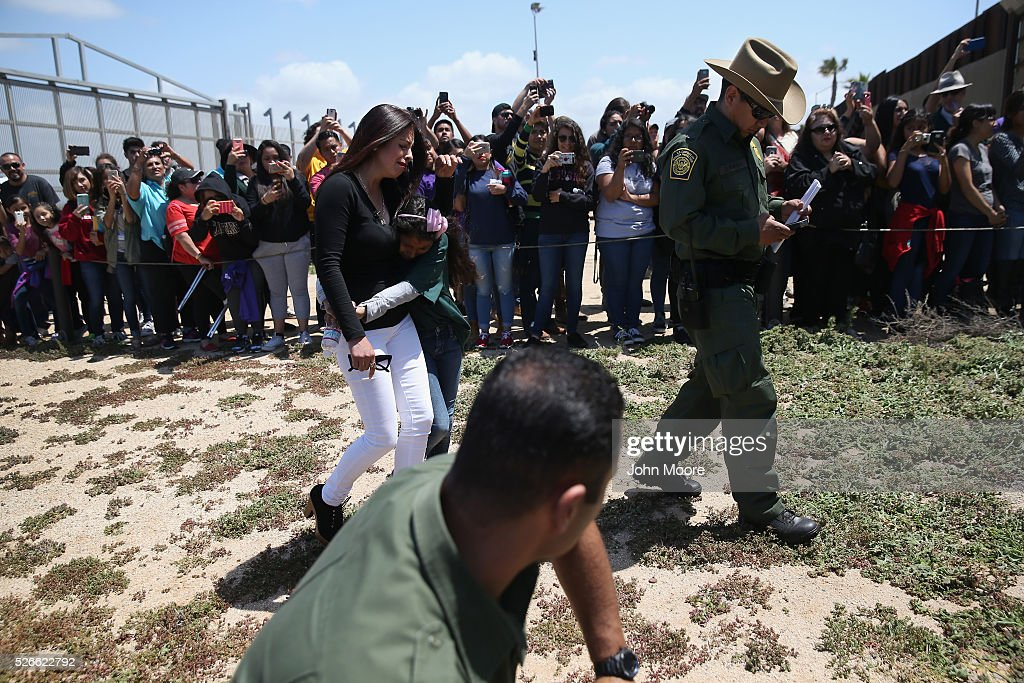 Family members, escorted by a U.S. Border Patrol agent, walk to embrace loved ones at the U.S.-Mexico Border fence during a 'Opening the Door of Hope' event on April 30, 2016 in San Diego, California. Five families, with some members living in Mexico and others in the United States, were permitted to meet and embrace for three minutes each at a door in the fence, which the U.S. Border Patrol opened to celebrate Mexican Children's Day. It was only the third time the fence, which separates San Diego from Tijuana, had been opened for families to briefly reunite. The event was planned by the immigrant advocacy group Border Angels.