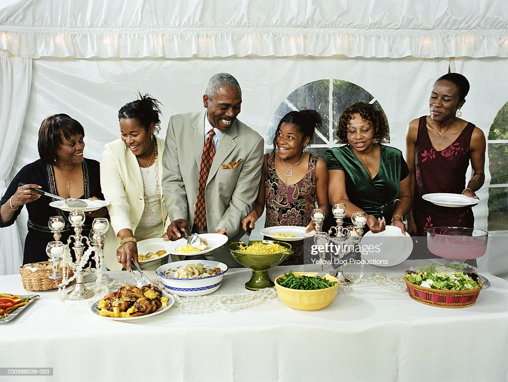 Family members filling plates at buffet table : Stock Photo