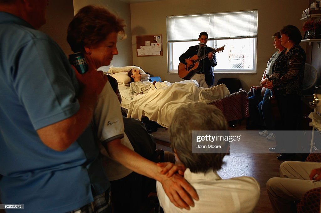 Family members gather around the bed of terminally ill hospice patient Linda Fletcher as musician Bob Haworth plays for her at the Hospice of Saint John on November 5, 2009 in Lakewood, Colorado. Haworth, a former member of the folk band The Kingston Trio, played songs from the 50's and 60's familiar to the elderly patients at the hospice. The non-profit hospice accepts patients regardless of their ability to pay, although most are covered by Medicare or Medicaid. End of life care has become a contentious issue in the current national debate on health care reform.