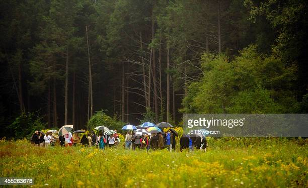 Family members gather in the rain at the impact site during 13th anniversary ceremonies commemorating the September 11th attacks near the Wall of...