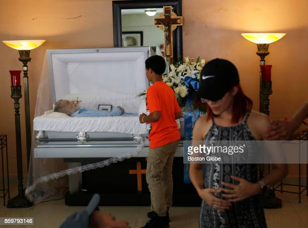 Family members gather to pay their last respects to Victor Ruiz Ramos in Corozal Puerto Rico on Oct 02 2017 After Hurricane Maria Ruiz used his car's...