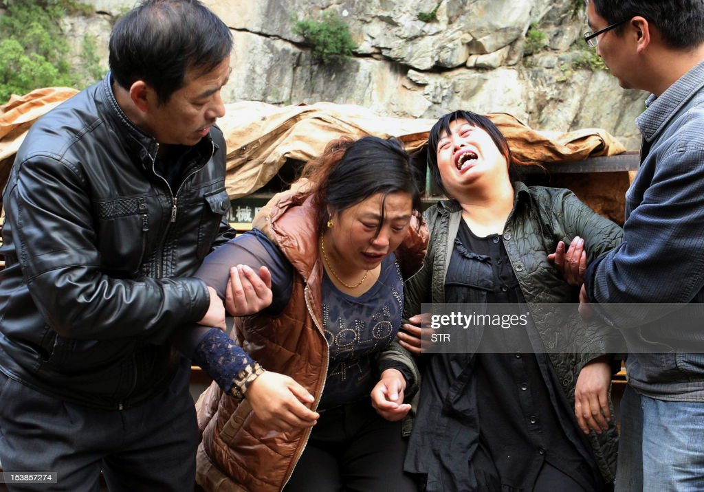 Family members grieve after discovering that their loved ones were among the 12 Chinese construction workers killed in a fire at their dormitory at a water-diversion project in Zhouzhi county of Xian, in the northwestern province of Shaanxi on October 10, 2012. Twelve Chinese construction workers were killed and 24 injured in a fire at their dormitory early October 10, state media reported. CHINA