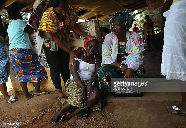 Family members grieve as Ebola burial team members prepare to remove the body of Nama Fambule for cremation on October 10 2014 in Monrovia Liberia...